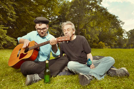 Two men on city park summer meadow enjoying day with guitar