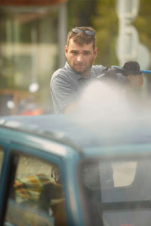 Man in car wash take care of his lovely retro car Stok Fotoğraf
