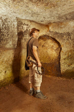 Adventurer in ancient cave on trace of mysterious emerald tablet finding famous artifact Stok Fotoğraf