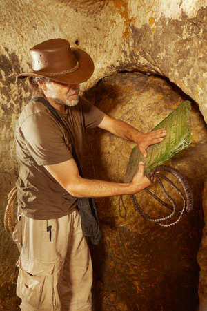 Adventurer in ancient cave on trace of mysterious emerald tablet finding famous artifact Banco de Imagens