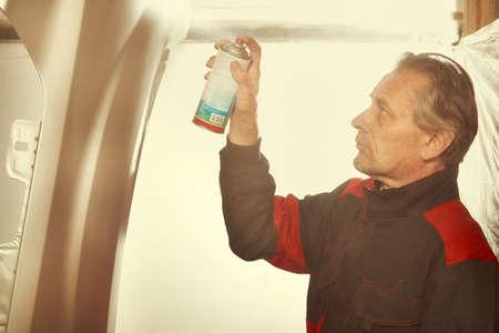 Man spraying and repairing in basement car fender for replacing