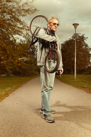 Older city man vagabond in hooded carrying scooter in late day city park