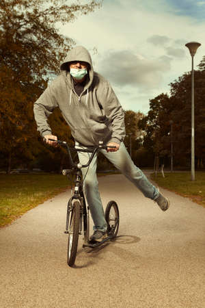 Older city man vagabond in hooded shirt with mask on scooter