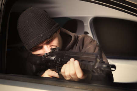 Man with assault carbine waiting for his victim inside car