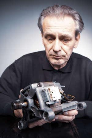 Man checking and measuring washing machine engine
