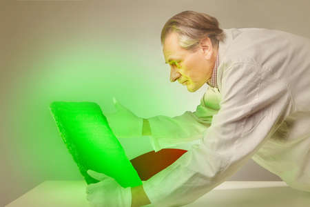 Museologist examining artifact of emerald tablet on his workplace
