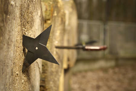 Four blade style classic hira shuriken weapon stuck into the target