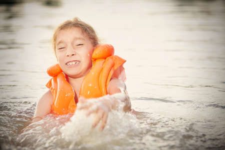 Little girl learning swimming in life jacket in natural water Foto de archivo