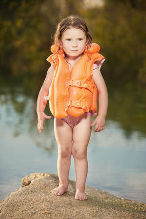 Little girl posing in life jacket by lake