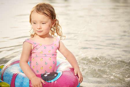 Little girl enjoying summer water with swimming ring Foto de archivo