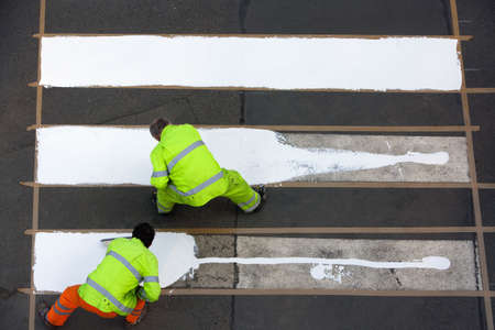 paso peatonal: trabajadores de paso de peatones con pintura de color blanco - vista desde arriba