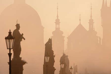 charles bridge prague at dawn during foggy morning