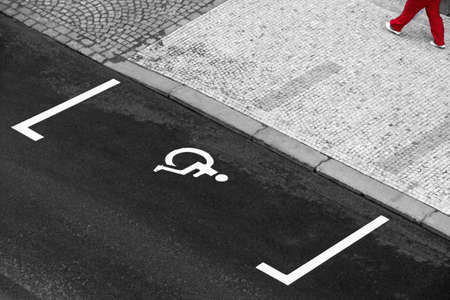 empty handicapped parking lot on a street - legs of bypasser on pavement