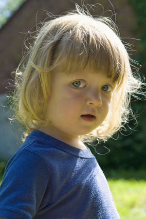 outdoor portrait of a beautiful boy with long blond hair