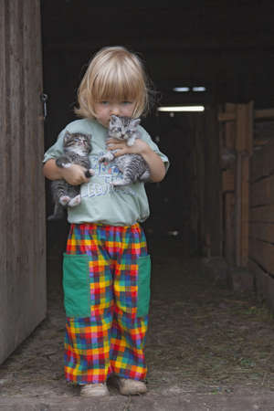 blond boy holding two kittens at the stable door Stock Photo