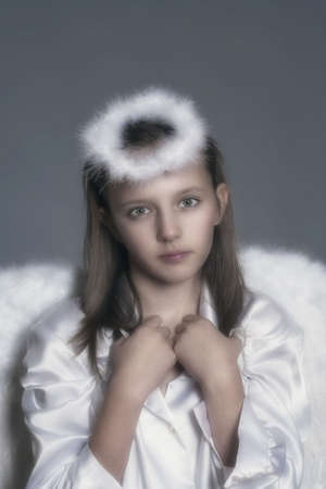 studio portrait of an eleven years old girl dressed as angel photo