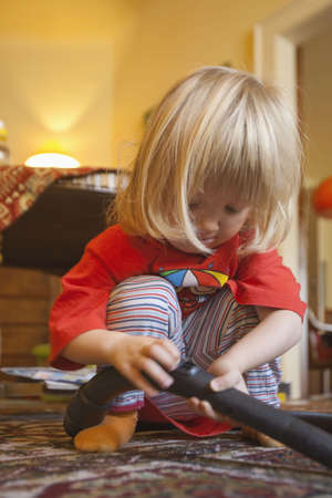 boy with long blond hair helping with vacuum cleaning photo