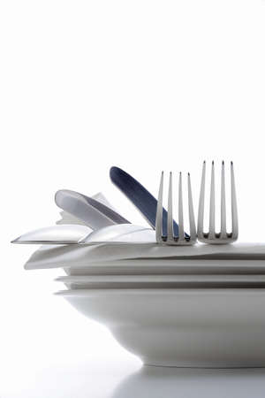 closeup of silverware on pile of plates with white cloth