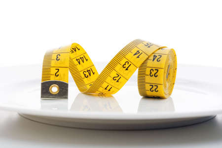 diet - yellow measuring tape on white plate isolated on white background
