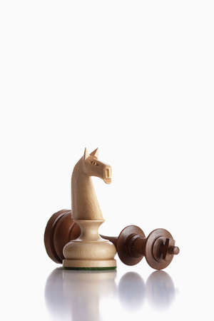 defeated: chess - white knight standing over defeated black king Stock Photo