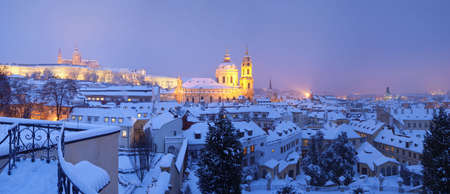 prague - panorama of hradcany castle and st. nicolaus church in winter