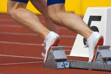 sport - runner at starting block in running competition Stock Photo