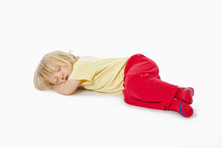 beautiful boy with long blond hair sleeping on the floor