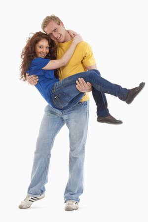 happy young couple - boy carrying girl in his arms - isolated on white photo