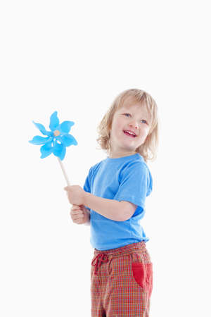studio shot of a boy playing with pinwheel - isolated on white photo