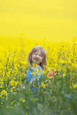 boy with long blond hair holding pinwheel in canola field photo