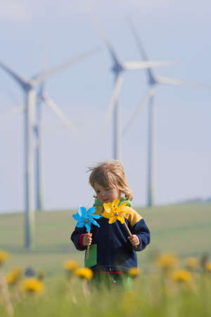 boy with long hair holding pinwheels standing in front of wind turbines