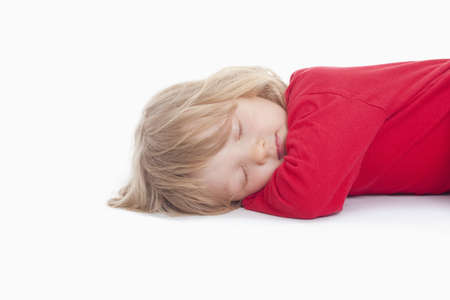 boy with long blond hair lying down sleeping - isolated on white photo