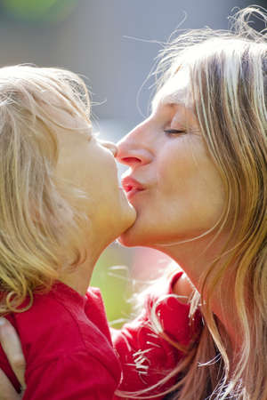 mother kissing her son with long blond hair outdoors photo