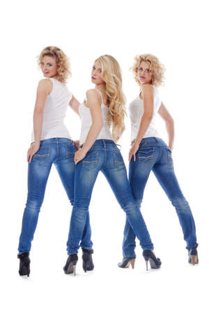 three young women in casual clothing standing,  looking - isolated on white photo