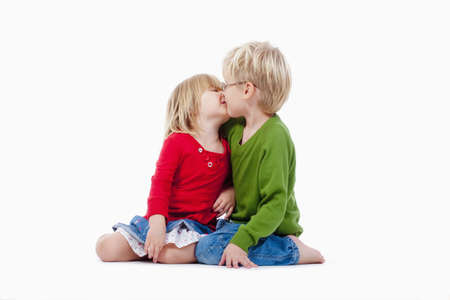 little boy and girl: children - brother and sister kissing each other - isolated on white Stock Photo