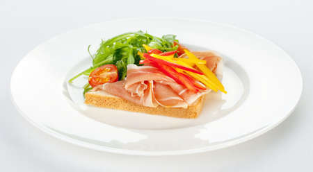 sandwich with ham, tomatoes, paprika and ruccola on a white plate photo