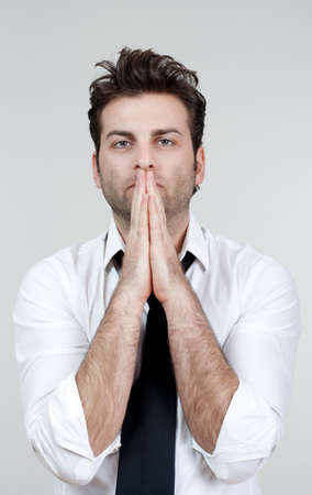 businessman in white shirt and tie holding hands together, praying - isolated on gray Stock Photo