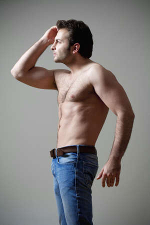 young shirtless musculous man in jeans looking - isolated on gray photo