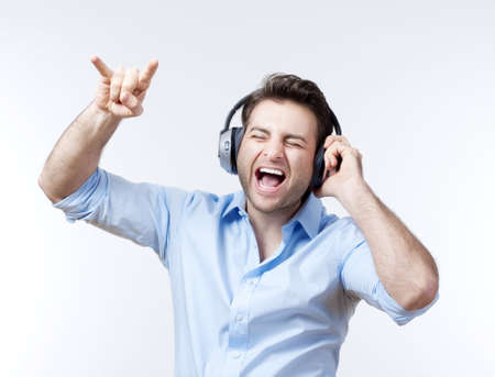 man in blue shirt with earphones listening to music - isolated on gray Stock Photo