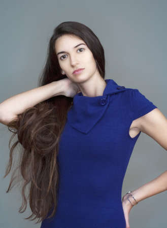 beautiful woman in blue dress with long brown hair - isolated on gray photo