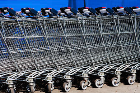 a line of empty supermarket shopping carts against blue wall photo