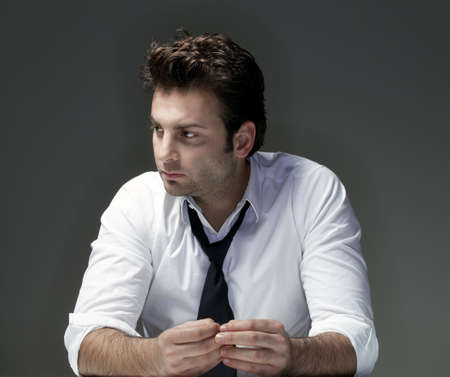 businessman in white shirt and tie, concerned, worried - isolated on gray Standard-Bild