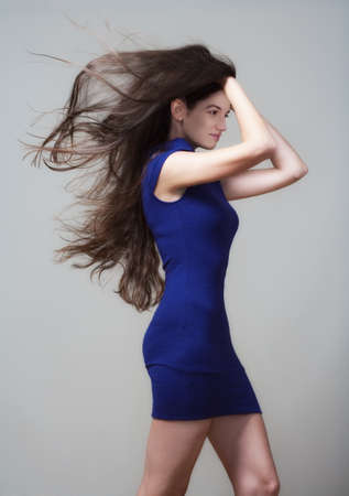 beautiful woman in blue dress with long brown hair flying - isolated on gray photo