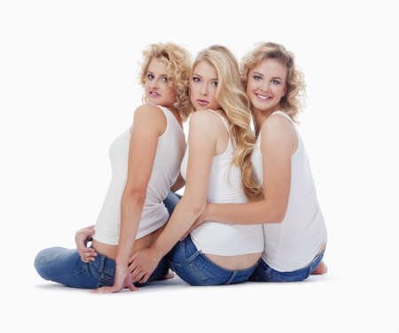 three young women sitting on the floor, looking up- isolated on white photo