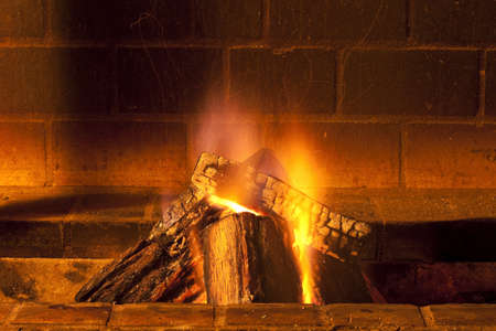 brick fireplace with large pieces of wood burning giving warmth photo