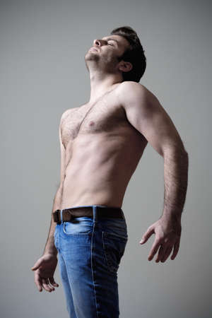 man arm: young shirtless musculous man in jeans standing - isolated on gray Stock Photo