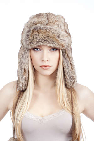 beautiful blond girl with blue eyes in fur hat - isolated on white photo