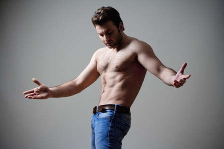 young shirtless musculous man in jeans - isolated on gray photo