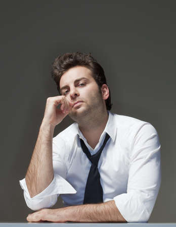 worried executive: businessman in white shirt looking, thinking - isolated on gray Stock Photo