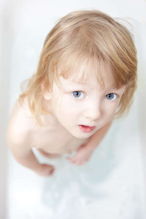 boy with long blong hair standing in bathtub looking up photo